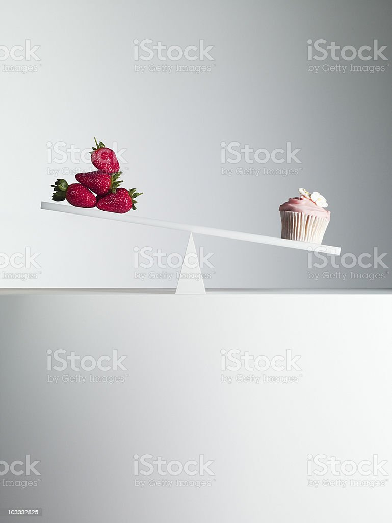 Cupcake tipping seesaw with strawberries on opposite end royalty-free stock photo