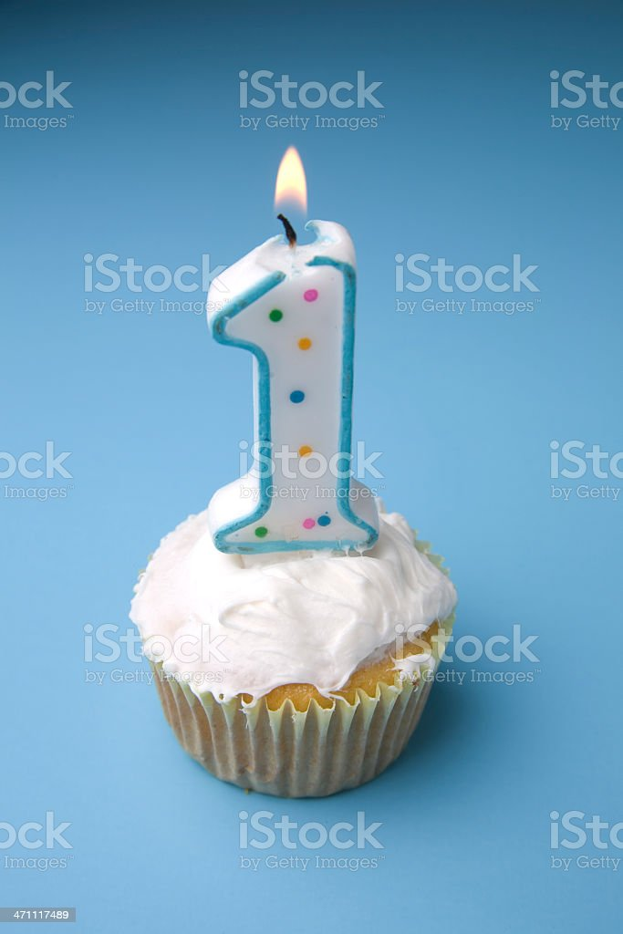 A cupcake with a 1 candle against blue background royalty-free stock photo