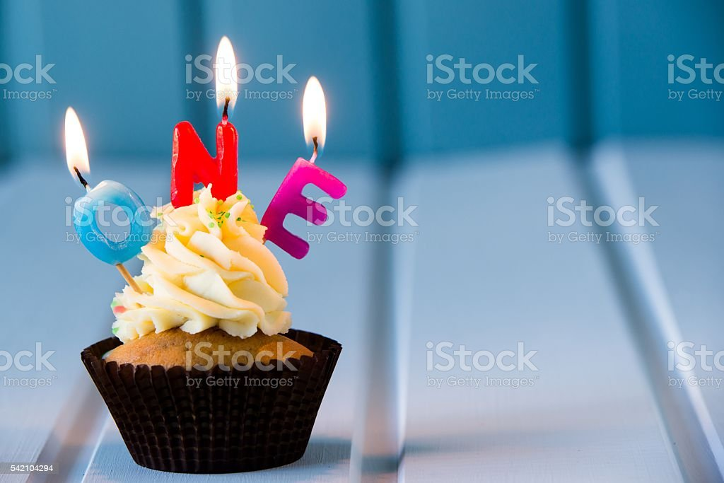 cupcake with a candles for 1 - first birthday stock photo