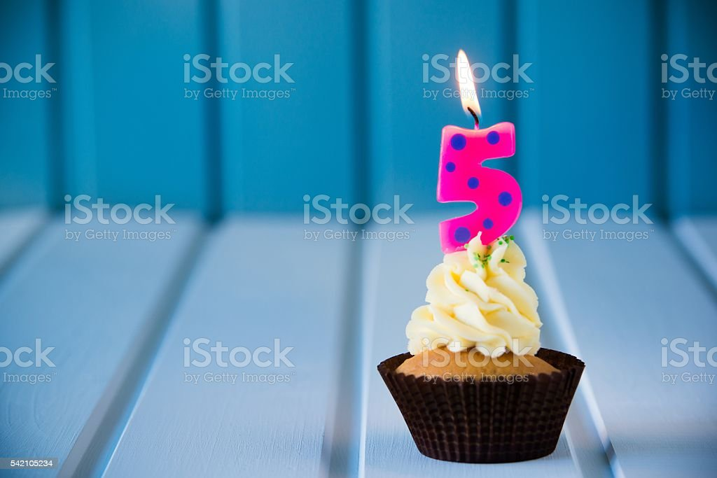 cupcake with a candles for 5 - fifth birthday stock photo