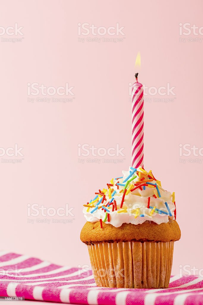 Cupcake with lit candle and confetti stock photo