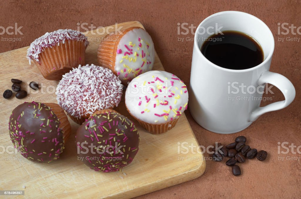 Cupcakes are different and a cup of black coffee on wooden cutting...