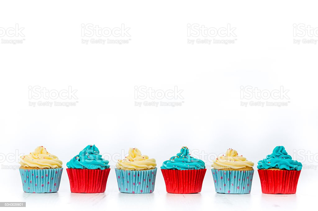 Cupcakes in blue,red and butter cream on white background stock photo