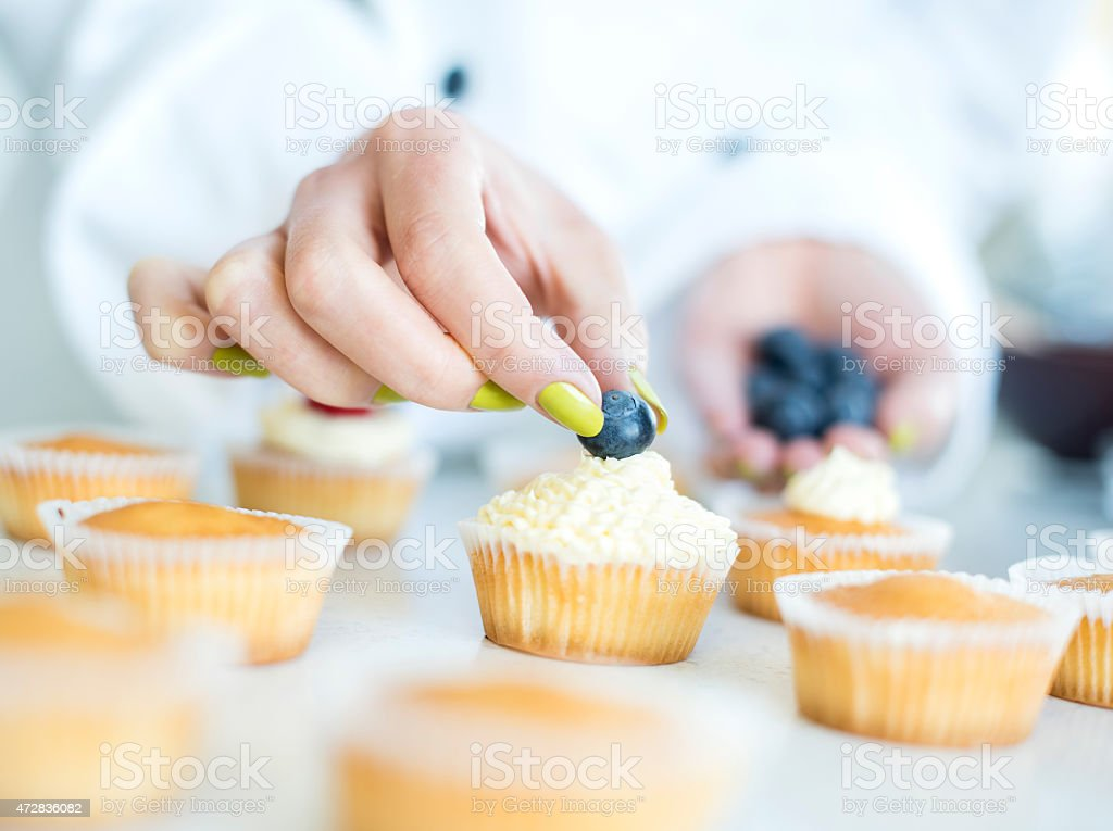Woman Decorating Cupcakes woman decorating a cake pictures, images and stock photos - istock