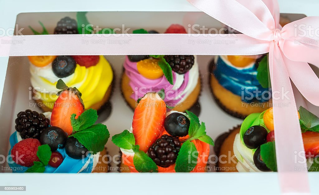 Cupcakes with berries in a gift box with a bow. stock photo