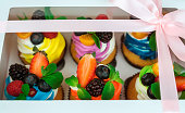 Cupcakes with berries in a gift box with a bow.