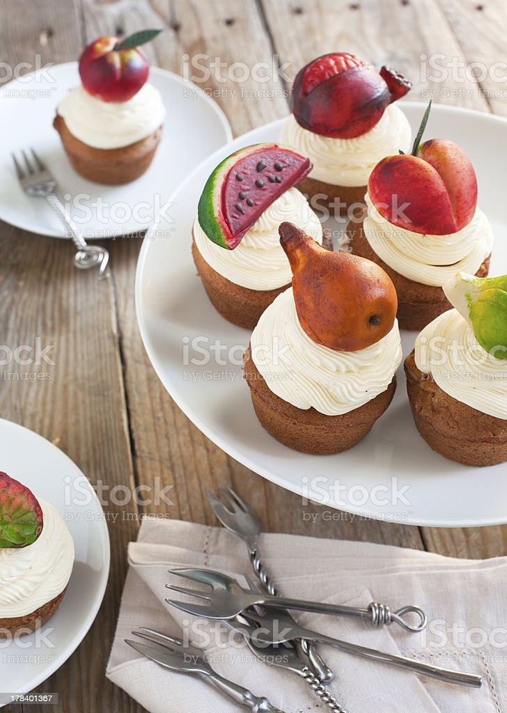 Cupcakes with vanilla buttercream and marzipan fruits royalty-free stock photo