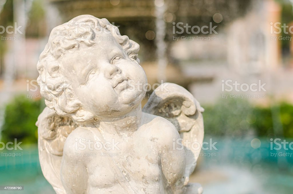 Cupid statue summer time background stock photo