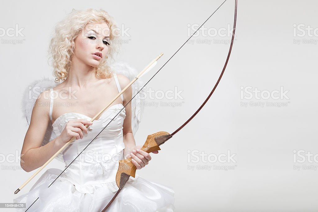 Cupid. Young beautiful blond woman in angel costume holding bow stock photo
