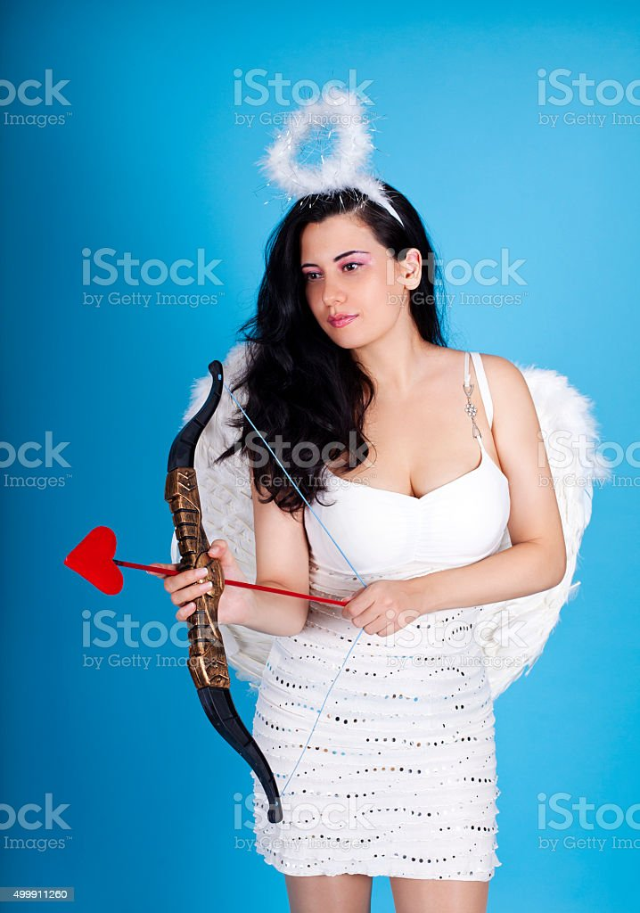 Cupid Young beautiful woman in angel costume holding bow stock photo