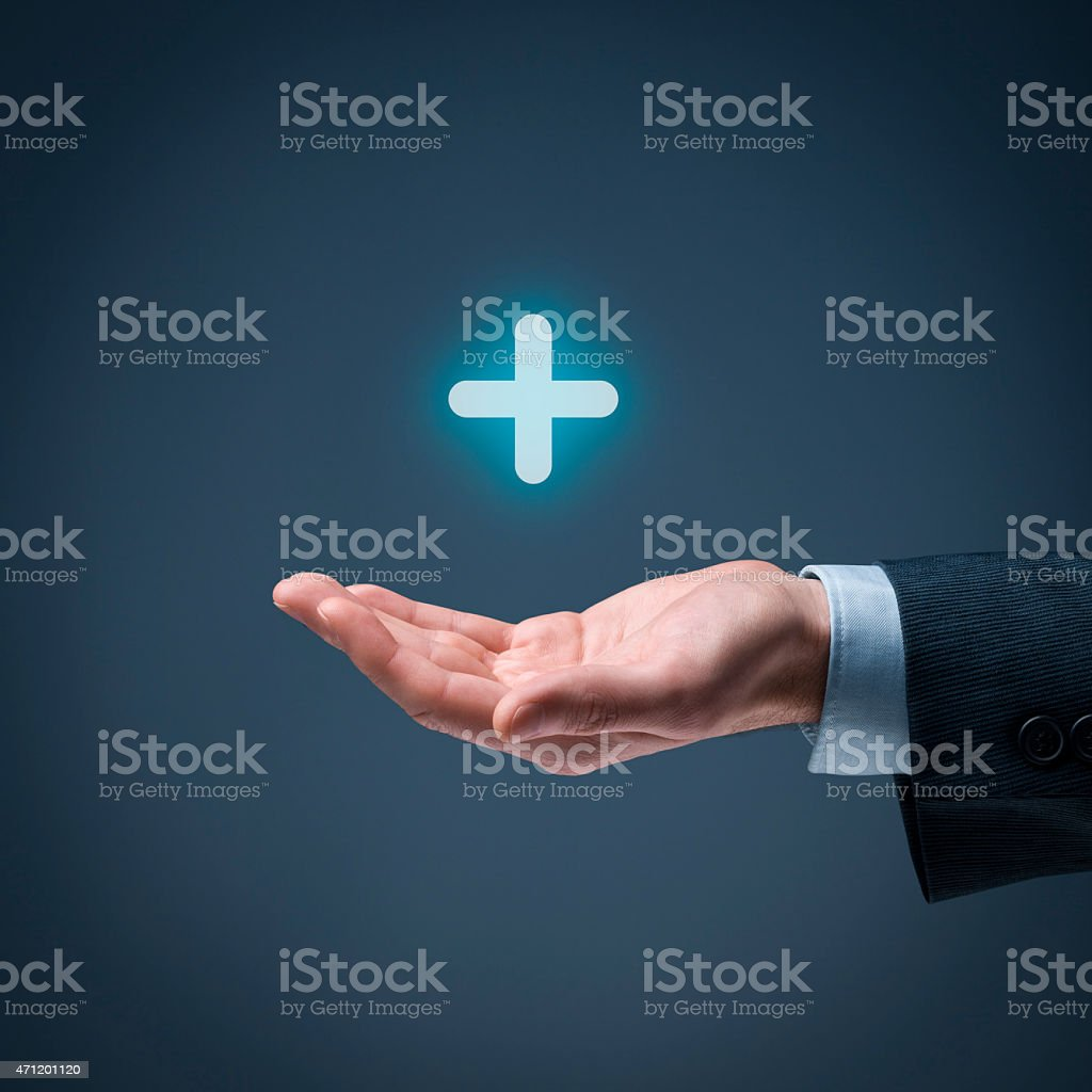 Cupped hand with a glowing plus symbol hovering above stock photo