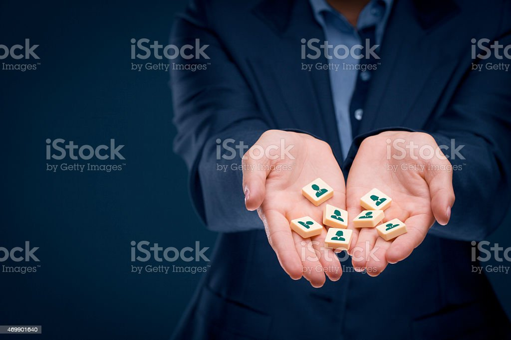 Cupped hands holding tiles with human resource icons stock photo