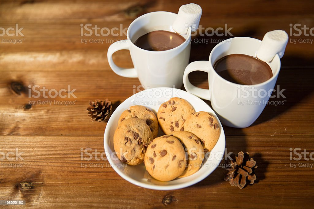 cups of hot chocolate with marshmallow and cookies stock photo