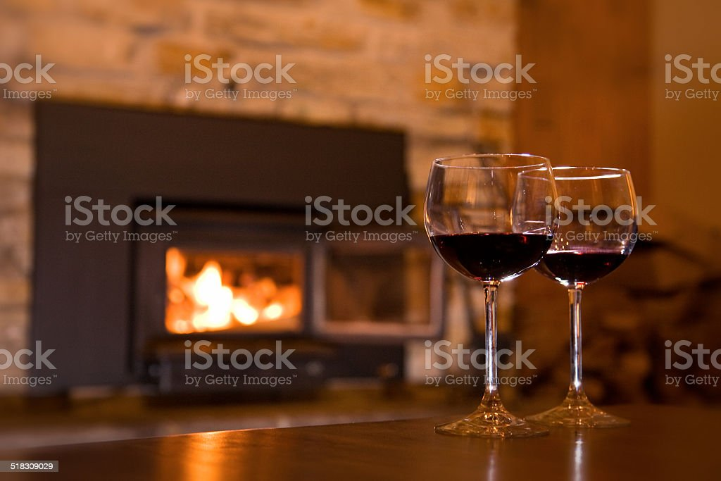 Coupes de vin sur une table devant un feu stock photo