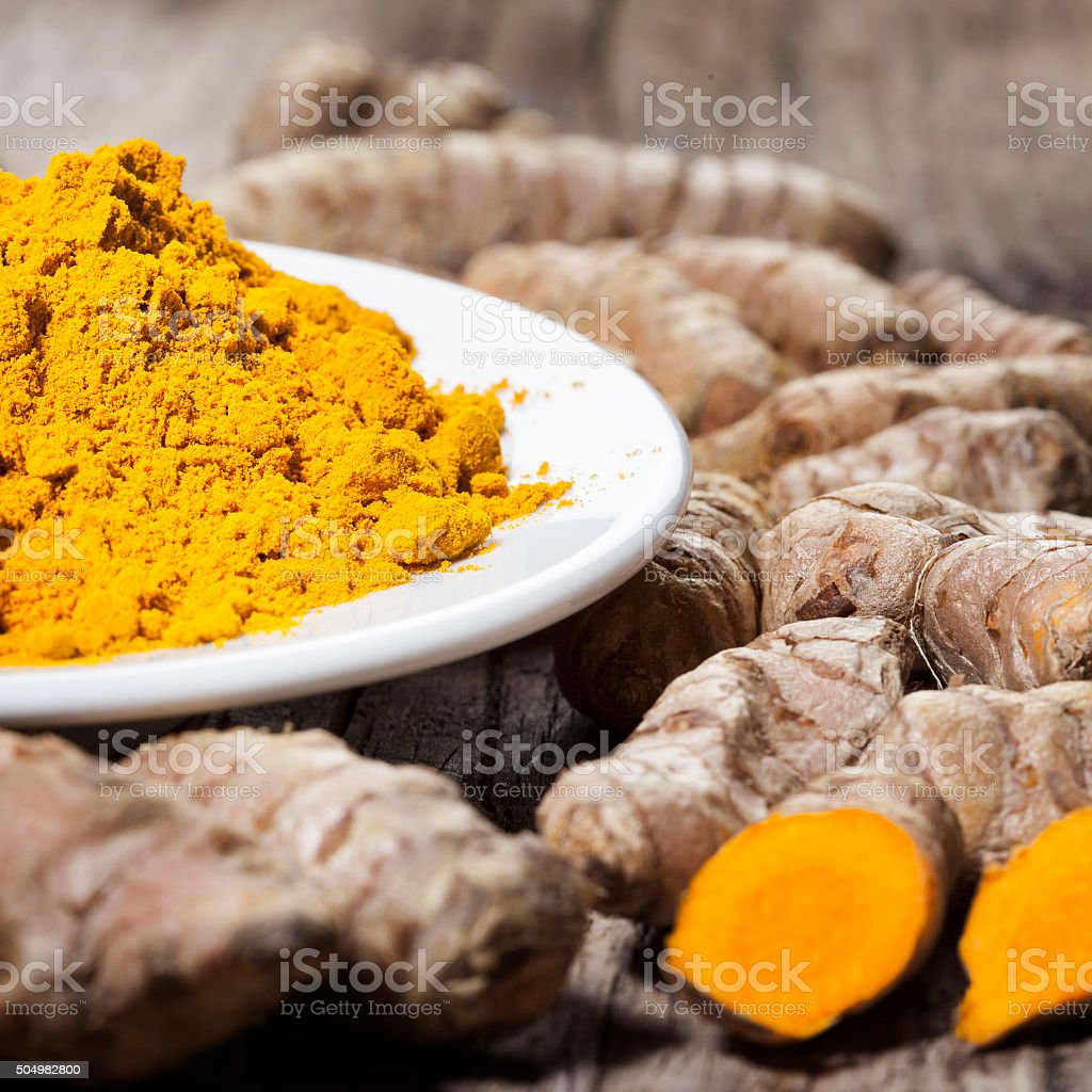 Curcuma rhizomes and powder alternative medicine stock photo