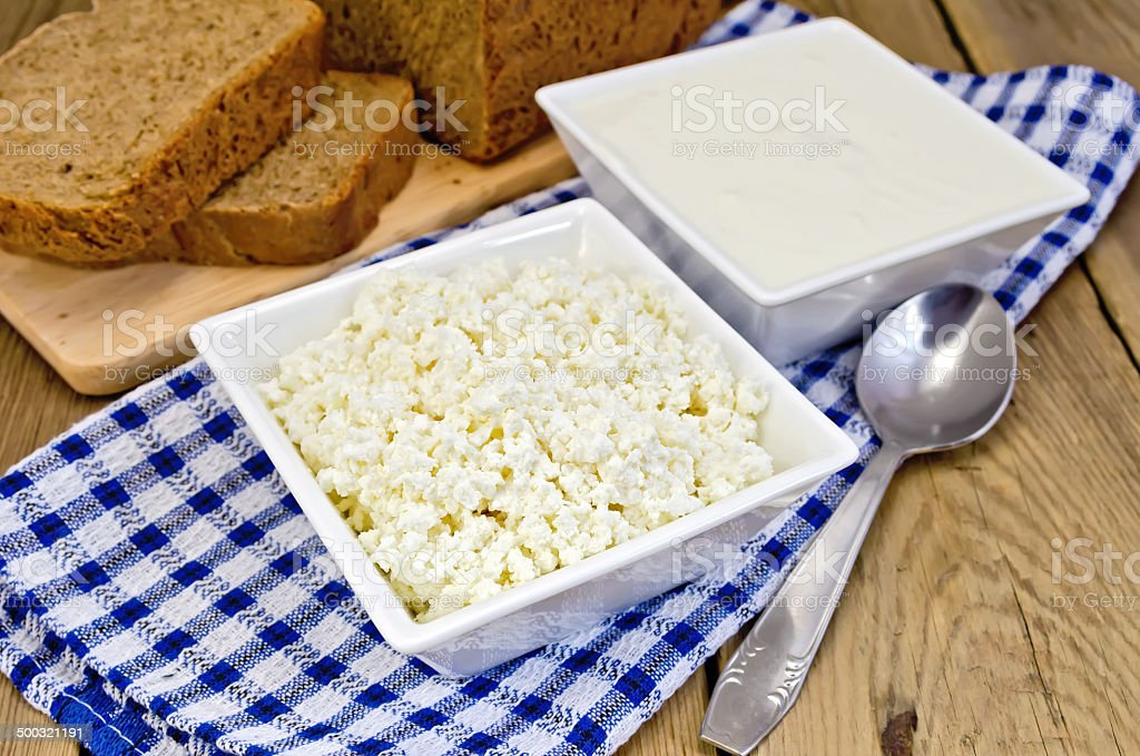 Curd and sour cream in bowls on board with bread stock photo