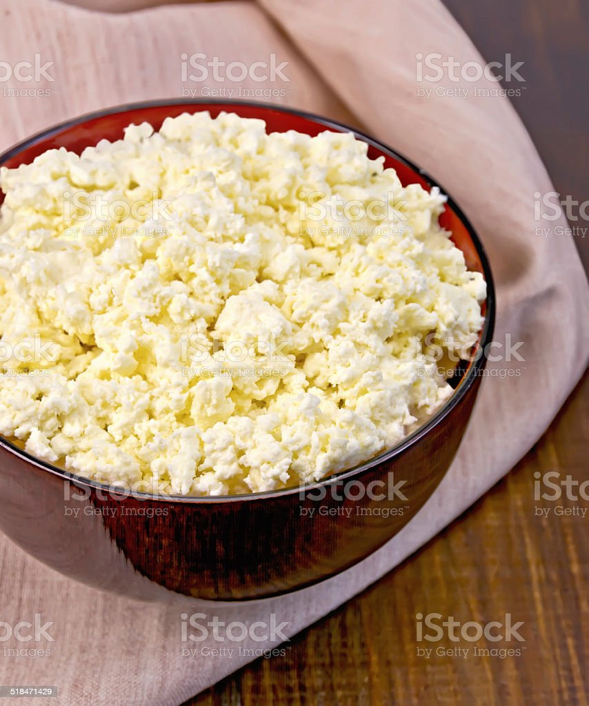 Curd in wooden bowl with napkin on board stock photo