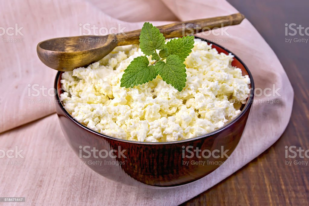 Curd in wooden bowl with spoon and mint on napkin stock photo