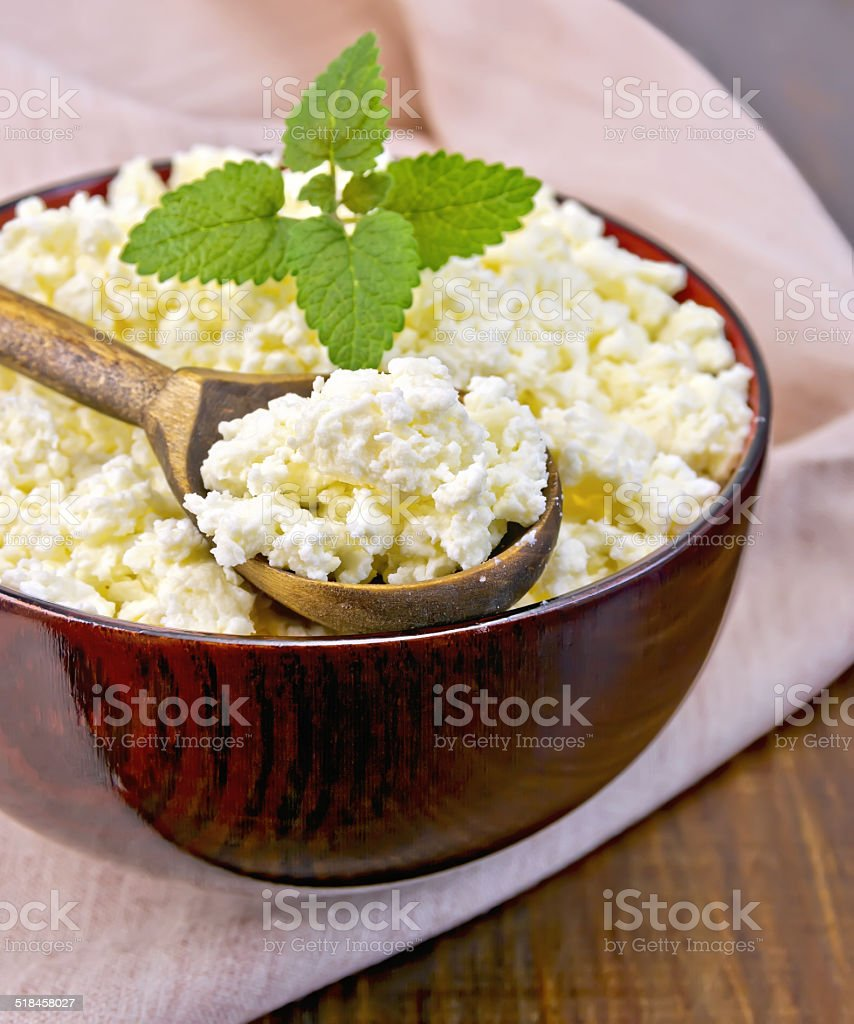 Curd in wooden bowl with spoon on board stock photo