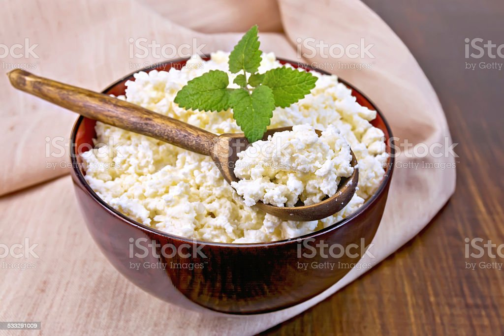Curd in wooden bowl with spoon on napkin and board stock photo