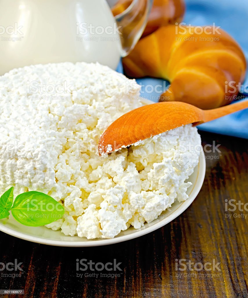 Curd on a saucer with a spoon on a board stock photo