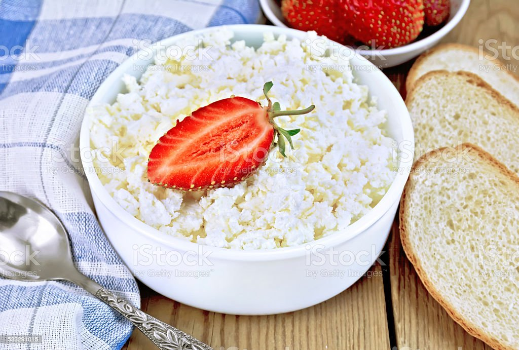 Curd with strawberries in bowl and bread on board stock photo