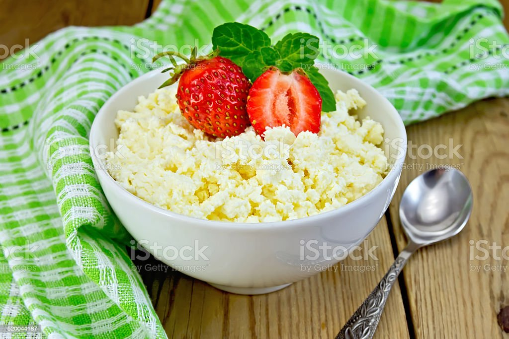 Curd with strawberries in bowl on board stock photo