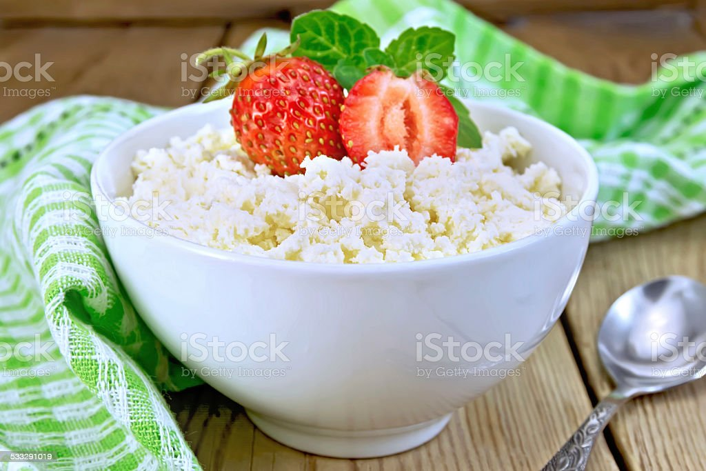 Curd with strawberries in white bowl on board stock photo