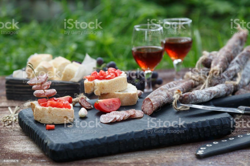 Cured dry sausage with wine, bread and tomato stock photo