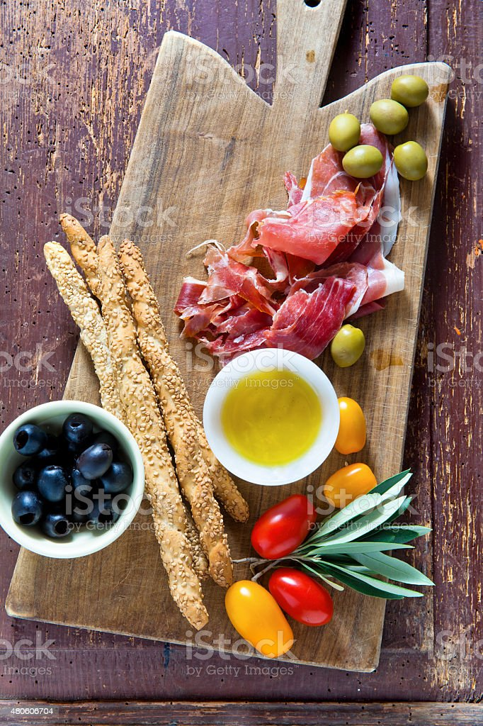 cured meat on a wooden cutting board with red tomatoes, stock photo