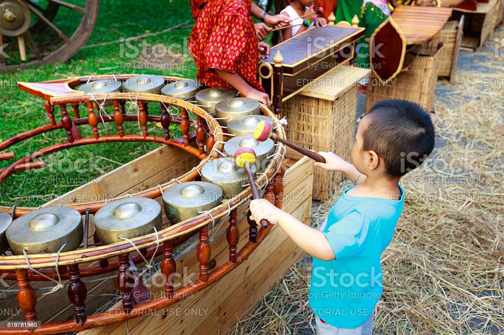 curious baby playing a traditional instrument in a culinary fairs stock photo