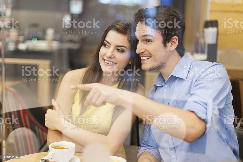 Curious couple looking away through window in cafe royalty-free stock photo