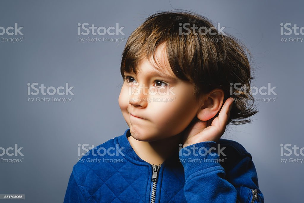 Curious Disappointed boy listens. Closeup portrait child hearing something, parents stock photo
