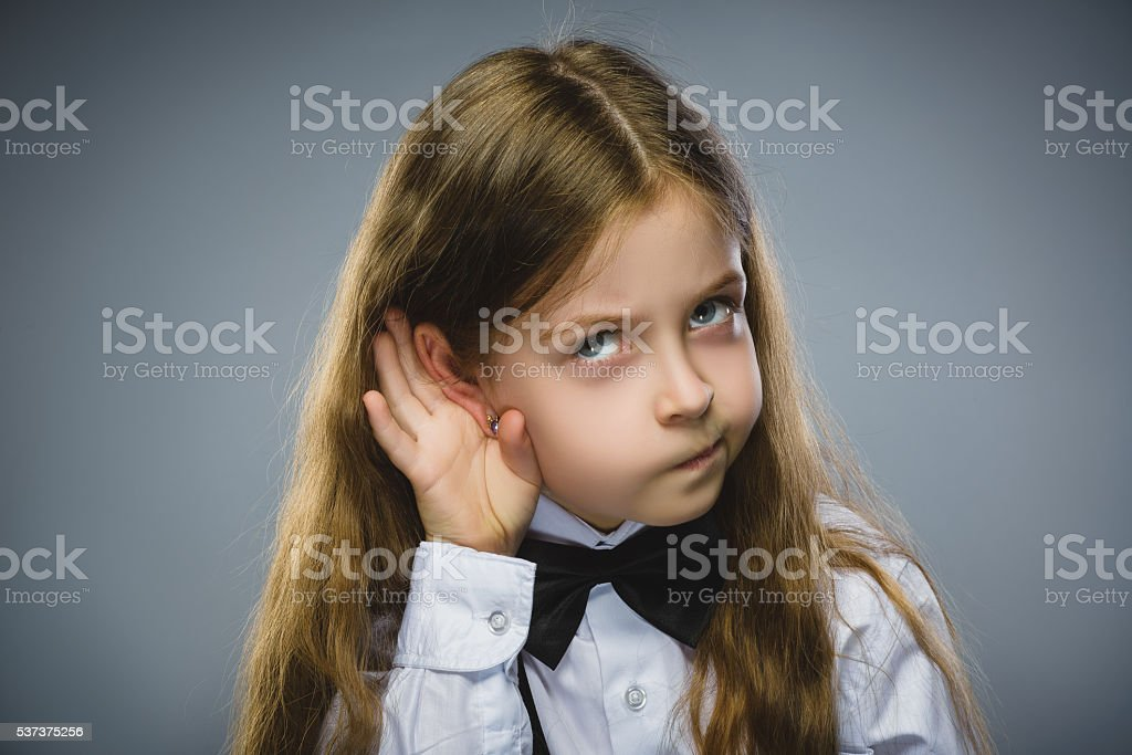 Curious Disappointed girl listens. Closeup portrait child hearing something, parents stock photo