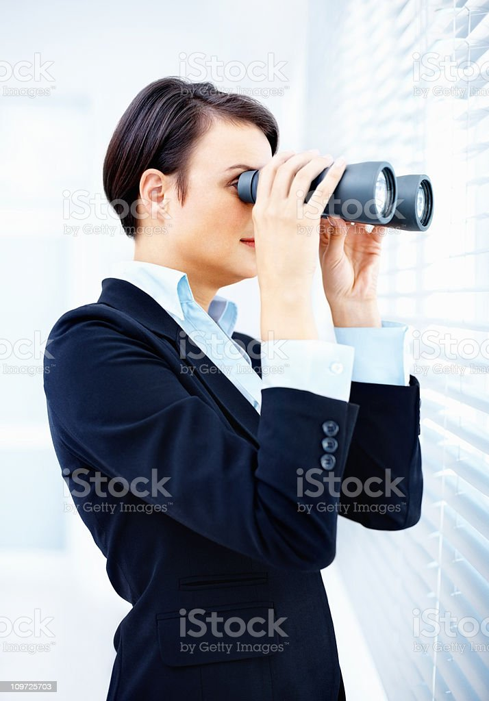 Curious female executive with binoculars looking through blinds royalty-free stock photo