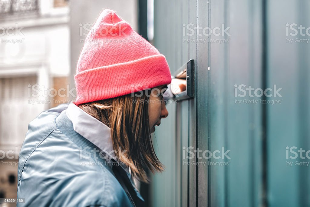 curious french teenage girl looking through letter slot at door stock photo