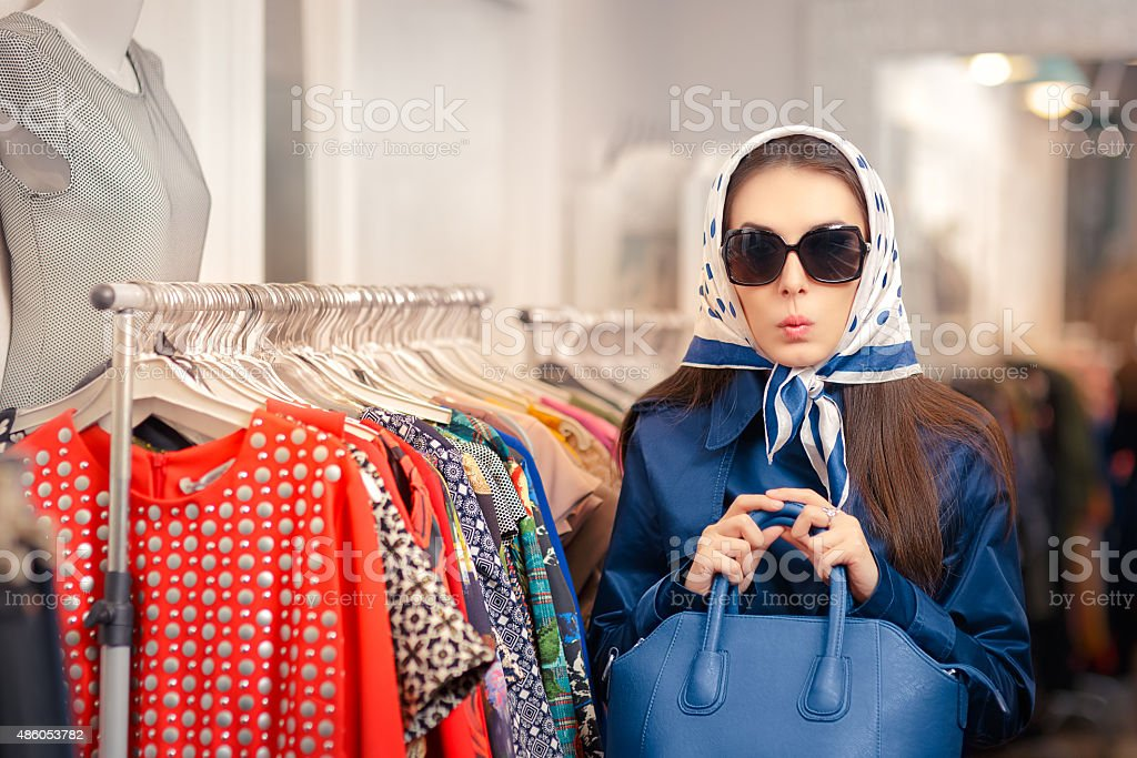 Curious Girl in Blue Trench Coat and Sunglasses Shopping stock photo
