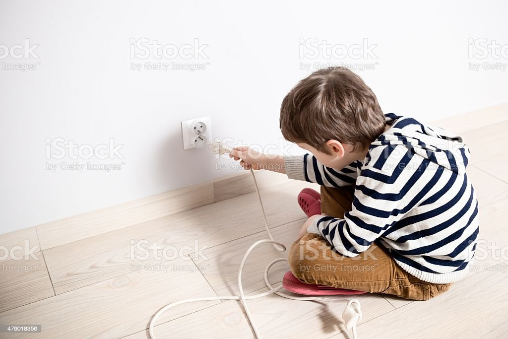 Curious little boy playing with electric plug. stock photo