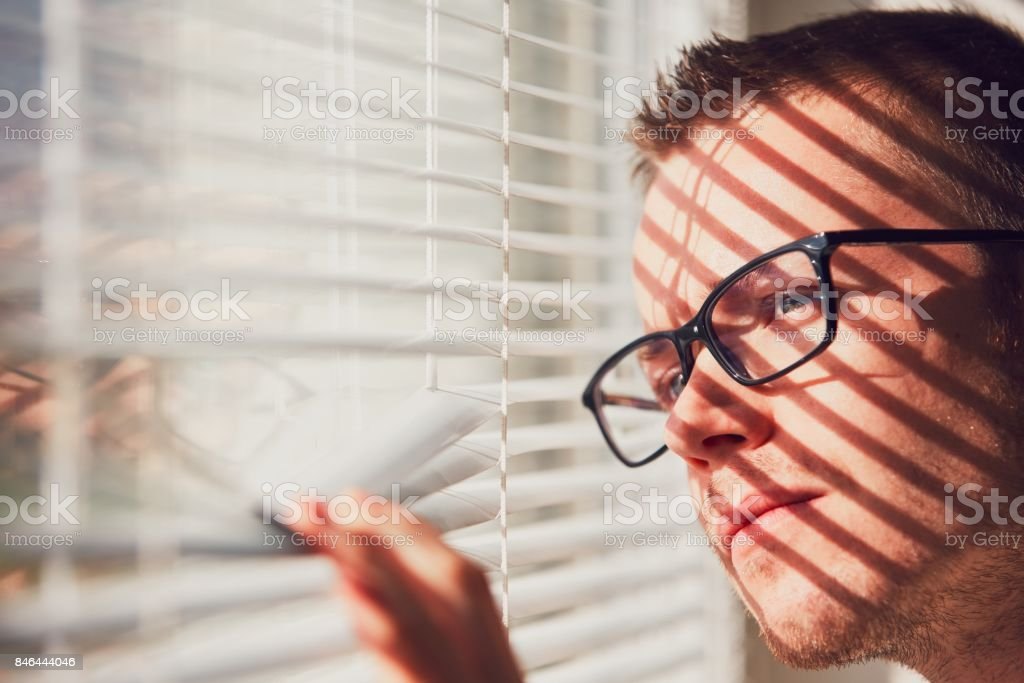 Curious man looking through a jalousie stock photo