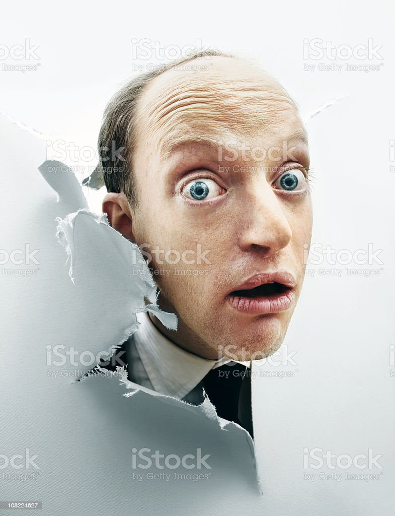Curious Man Poking Head Through Broken Canvas stock photo