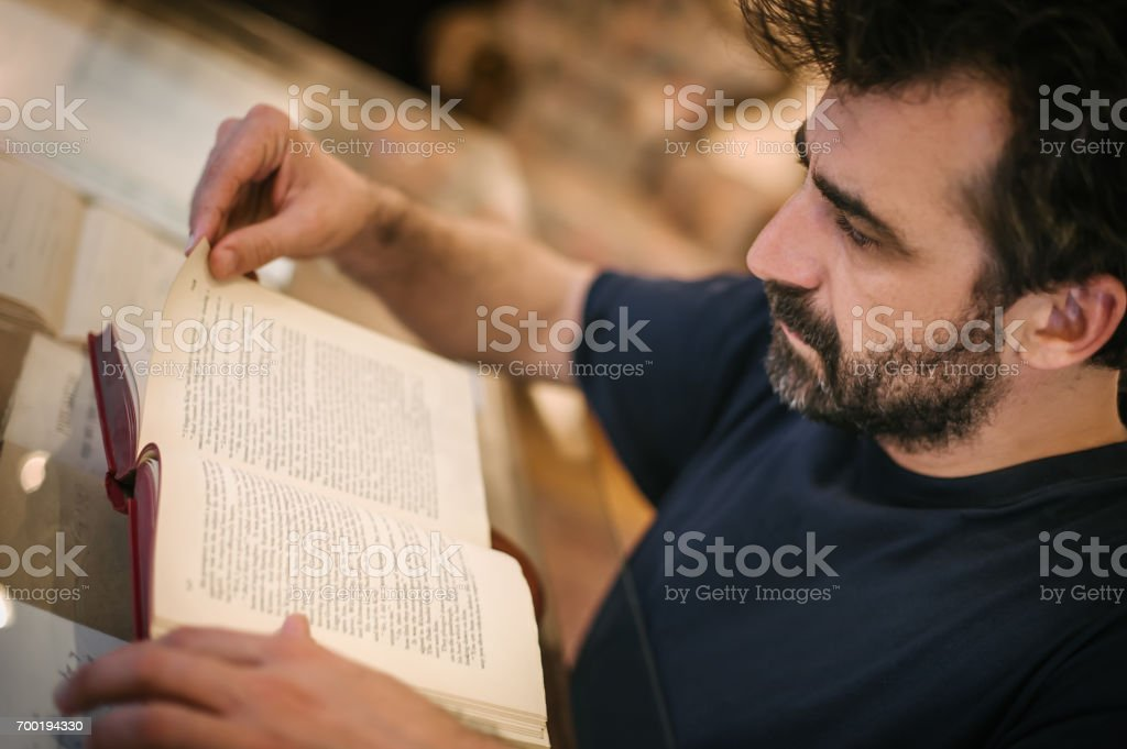 Curious man reading old book in his library at home stock photo