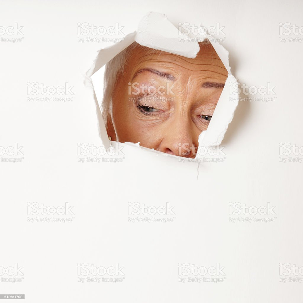 curious mature woman looking through hole stock photo