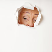 curious mature woman looking through hole