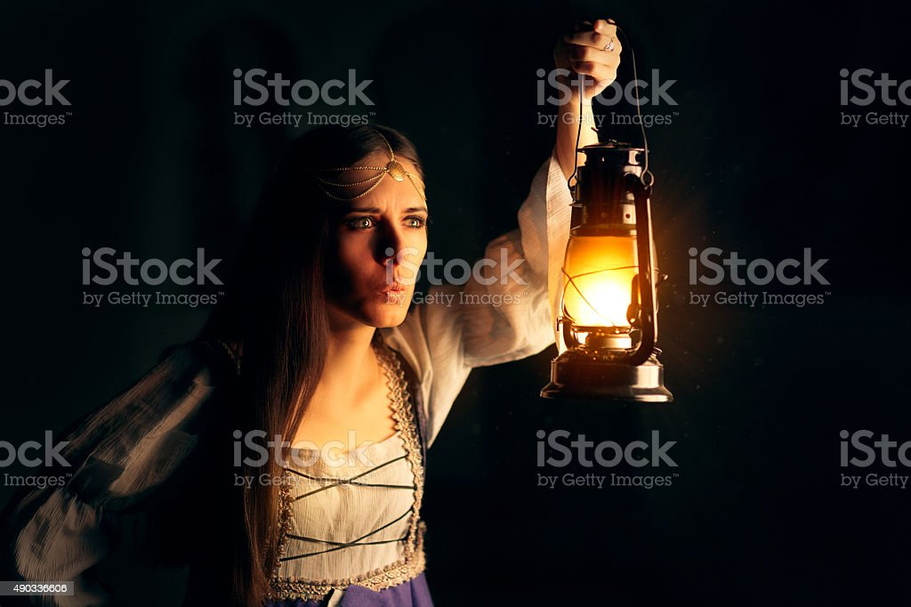 Curious Medieval Princess Holding Lantern Looking Outside stock photo