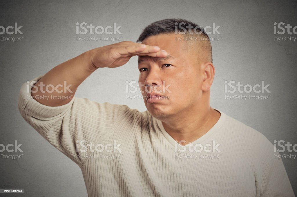 Curious middle aged man searching looking far away into future stock photo