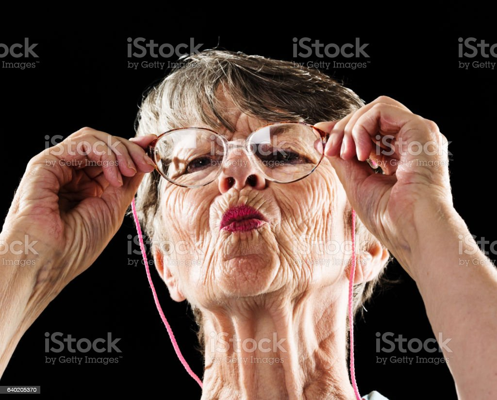 Curious old woman with pursed lips peers through spectacles stock photo