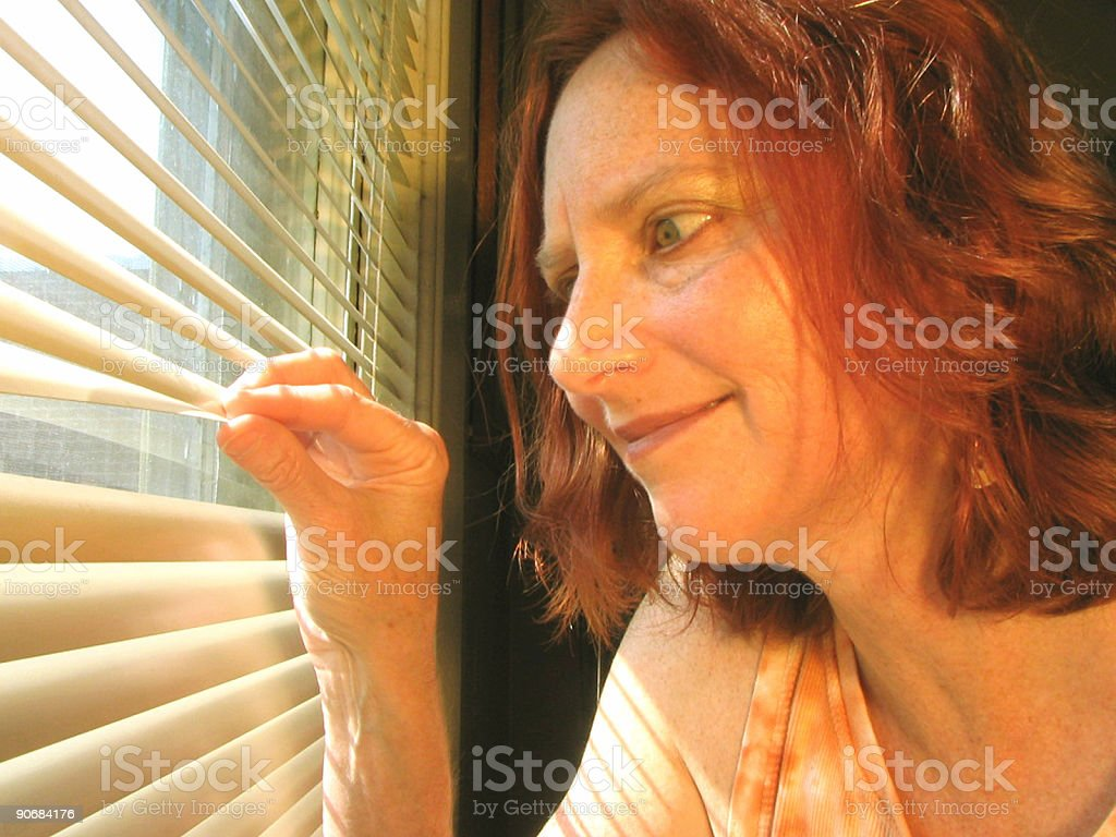 Curious Redhead Looks Out Window royalty-free stock photo