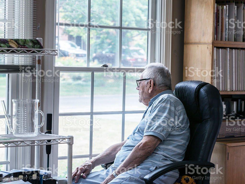 Curious Senior Man Looking Through Window stock photo