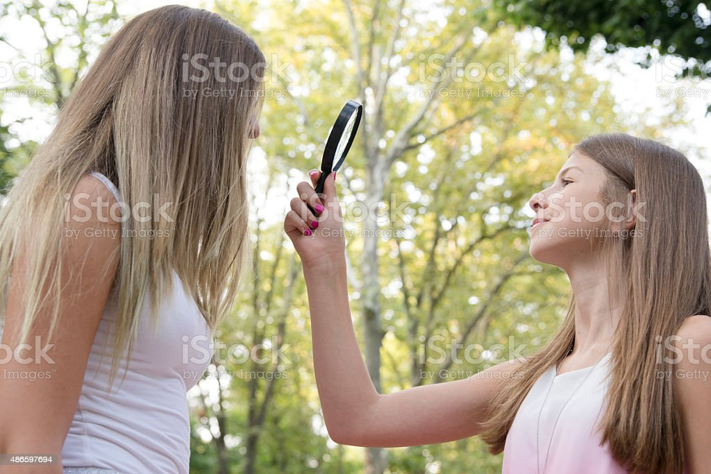 curious sisters with a magnifying glass stock photo