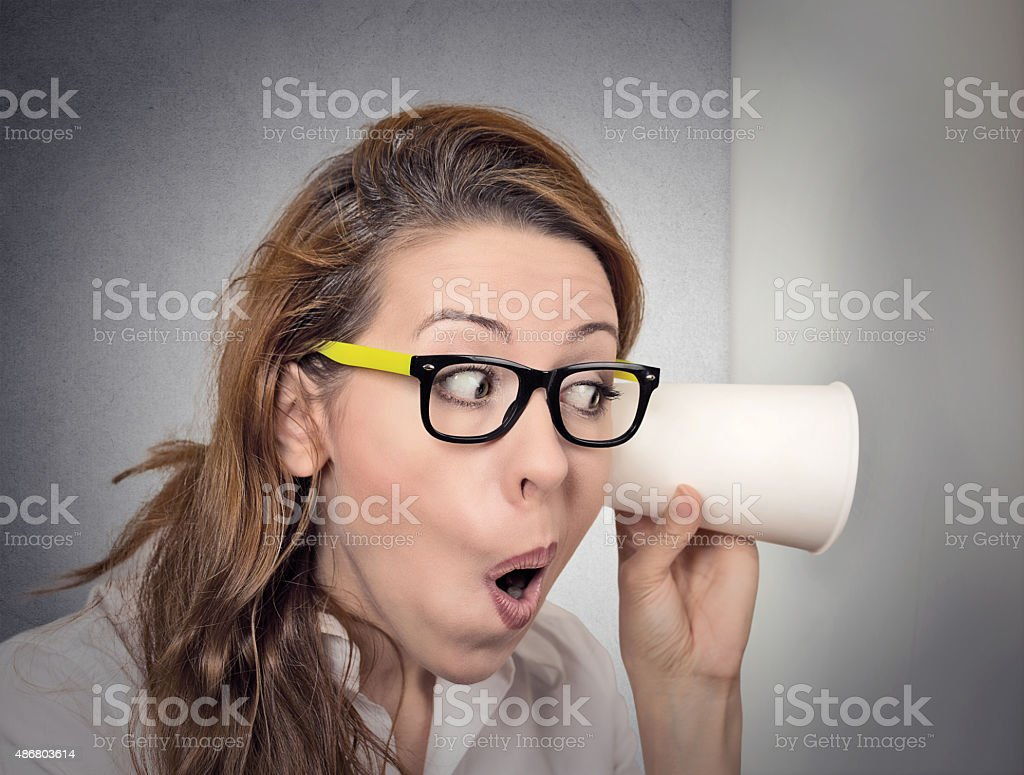 curious woman leaning against wall listening to conversation using cup stock photo